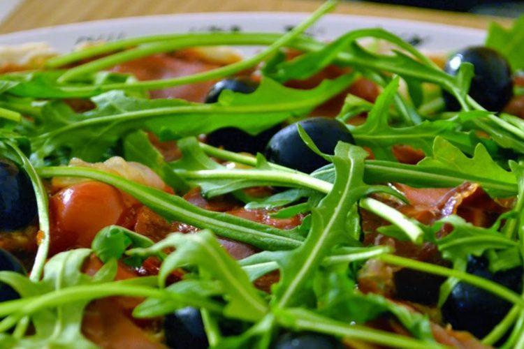 Pizza z rukolą, chorizo, szynką serrano i oliwkami  na ziołowym spodzie z mąki pełnoziarnistej